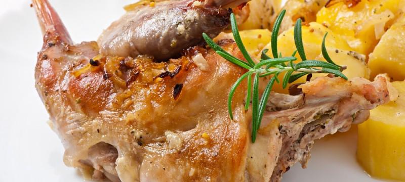 Conejo con láminas de patata, tomate y cebolla al horno